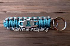 This multi-functional teal awareness ribbon paracord key fob is a great way to show support and raise awareness! The key fob can be taken apart and used in any number of emergency situations. It is made with 550 paracord. This key fob features a stainless steel charm/tag as well as a key ring, perfect for keeping your keys handy. This product is completely waterproof! It will not mildew or rot. Made in the USA!  Show support and raise awareness for ovarian cancer, cervical cancer, uterine…