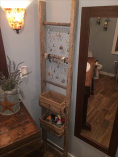 Old ladder used for bathroom organization. Could redo the vanity in the 1/2 bath with pallet wood and then use a ladder in the corner...