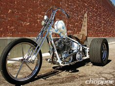 Evo Big Twin 70s-style softail trike with differential rear end, spool invader front wheel, narrow srpinger and brown king/queen seat with tall backrest | by Noise Cycles | left front