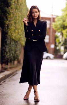 Sarah Donaldson usa blazer estruturado com saia preta midi e sandália de tiras