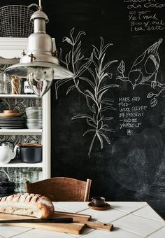 Kitchen details - an old kitchen cabinet without doors, an old wooden table with a top of ceramic tiles and a wall painted with blackboard paint for the small messages and checklists.