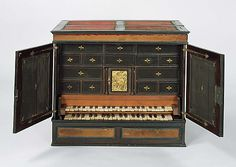 Claviorganum 1598 - This tiny instrument incorporates an organ and a virginal built into an ebony tabletop chest of drawers. The lower keyboard manual is for the organ, and levers at the left of the keyboard serve as stops. A pair of bellows is concealed beneath the top of the chest; two ranks of flue pipes and a regal (reed) stop are arranged behind the drawers in the back.