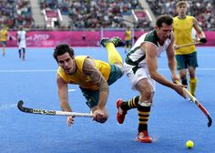 Australia's Kieran Govers, left, falls to the ground as he battles for ball possession with South Africa's Andrew Cronje during a men's field hockey preliminary match at the 2012 Summer Olympics, Monday, July 30, 2012, in London. (AP Photo/Bullit Marquez)