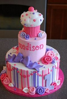 Three tier birthday cake with a girl with top tier a pink and white cupcake
