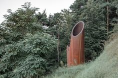 "MoDus Architects imagined the portals as ""expressive figures whose raised heads emerge from the buried, unseen networks"" of the roads hidden in the hillsides. Acoustic Barrier, Civil Engineering Projects, Weathering Steel, Alpine Village, Exposed Concrete, South Tyrol, Corten Steel, Entrance, Landscape"