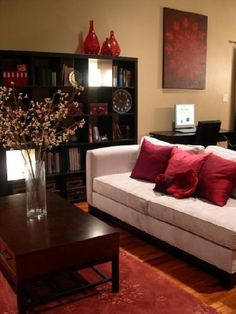 HGTV's RMS    Cozy bright living room! Gray velvet sofa, red silk pillows, red wool rug, wood coffee table, bookshelf bookshelves, red glass vases, office area and yellow green paint color walls! red black gray yellow green living room colors.