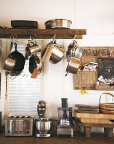 Hanging pots and pans from the ceiling frees cabinets of bulky equipment and creates visual interest too. Designer Jason Grant used a natural timber to create a rustic look — try a vintage ladder for a similar effect. Click for more ways to style small kitchens.