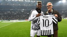 Paul Pogba (L) of Juventus gives his jersey to Alberto Cairo, Head of the Inter Committee of the Red Cross rehabilitation center in Kabul prior to their UEFA Champions League round of 16 first leg against Bayern