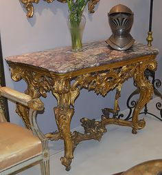 Very fine, Italian Rococo period console table: In solid, elaborately carved giltwood with Serravezza marble top, pierced skirt centered by a Rococo foliate ornament, complex volute floral and foliate-carved cabriole legs, and arched foliate stretcher. Mid-18th century.Provenance: Formerly part of the furnishings at The Audubon House, Key West, FL; previously on%