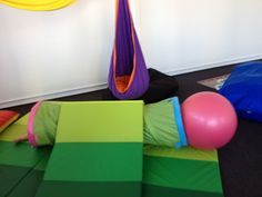 tunnel, mats and a swiss ball create a great obstacle for gross motor practice - crawling and pushing, motor planning and spatial awareness