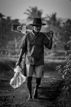 A senior person is heading to field, where he earns money from. Daily life in Indonesia.