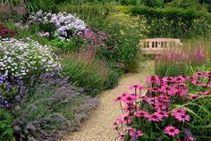 Cottage tuin met grindpad tussen de bloemen en houten bankje.