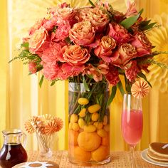 Create a centerpiece worthy of a 5-star restaurant. Fill a vase with oranges and water and add some brightly colored flowers.