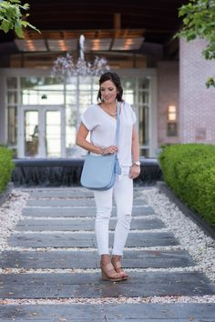 An all-white outfit with a serenity blue handbag and nude wedge sandals is the perfect modern summer outfit for women over 40!