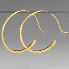Rosanne Pugliese's 'Tendril Hoops' are a modern take on classic hoops. She hand hammers recycled 22k yellow gold to form a perfectly fluid and light design, that exudes effortless style.