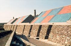 Umberto Riva Architetto. Casa di Palma, Stintino, Sardinia, Italy, 1959–1960.View showing exterior stone walls with oblique openings and roofs with coloured tiles. Photograph by Umberto Riva. © Umberto Riva.