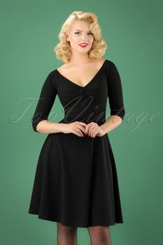 This50s Leonie Swing Dress in Black is just PERFECT!  STOP! Warning: continue reading at your own risk because Leonie is THE perfect Little Black Dress! She features a striking V-neckline, faux buttons with elegant pleats at the bust and 3/4 sleeves which will rest gracefully at the shoulders. She runs from the waist down into a flattering semi-swing skirt that will move playfully with every step you take. But that's not all, she's made from a thicker yet supple and stretchy fab...
