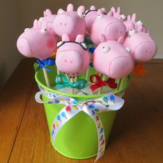 Peppa pig cake pops in Peppa, George, Mummy and Daddy with matching ribbons. Displayed in a decorative bright green bucket