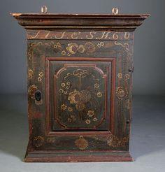 Rosemalt hengeskap med eierinitialer og dat. 1760. H: 78 cm., B: 67 cm., noen mangler.