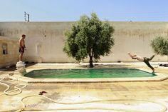 TAKING A BREAK: A Free Syrian Army fighter dove into a swimming pool as a fellow fighter watched in Aleppo, Syria, Monday. (Hamid Khatib/Reu...