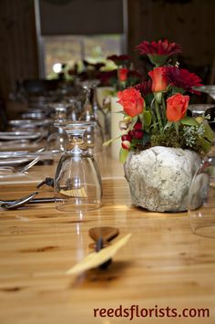 """Gerberas, roses and orchids in a unique """"stone"""" container repeated along the bare wood tables complete the rustic theme. Wedding Designers, Wood Tables, Wedding Decorations, Table Decorations, Lodge Wedding, Rustic Theme, Orchids, Glass Vase, Floral Design"""
