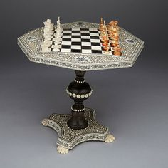 "ANGLO INDIAN MINIATURE IVORY AND HORN GAME TABLE AND CHESS SET, VIZAGAPATAM, C.1840 with white and red pieces on an octagonal veneered sandalwood top board top on turned support on quadripartite base raised on paw feet, with, table width 24"" - 61 cm"