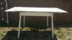 white, wooden table, with drop leaf extenders on both sides