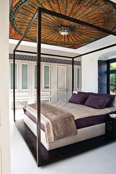 Idra: Una dimora antica rivisitata dall'interior designer Tina Komninou. Il pannello a mosaico e il letto a baldacchino sono il fulcro di questa camera da letto.
