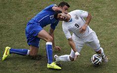 Italy's Andrea Barzagli tackles Uruguay's Luis Suarez