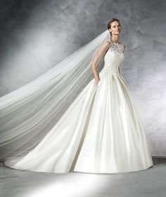 The New Design Mikado silk princess-style wedding dress. Bodice with soutage and underbodice with bateau neckline. Round neckline at the back. Wide pleated mikado silk skirt with side pockets Free Measurement