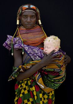 Albino baby girl and her Mumuhuila tribe mother -Angola This albino baby girl had some little dreadlocks & was incredibly white. The mother was proud to pause for the picture. This is beautiful. by Eric Lafforgue