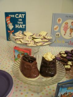 Cute chocolate candy booties filled with baby candy items, book candy behind them.
