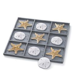 """shell tic-tac-toe décor -    Sure to invite comments, this decorative tic-tac-toe game brings a feel of the sea into your home. Beautifully crafted resin starfish and sand dollars form the x's and o's -- the set comes with 5 each, as well as a resin tray with 9 compartments made to look like weathered wood. Measures 14"""" x 14"""". Imported."""