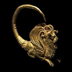 HELLENISTIC GOLD EARRING IN THE FORM OF A CROUCHING WINGED GRIFFIN Repoussed, the details are added with twisted gold wires of varying widths. The style is reminiscent of the carved reliefs found at Persepolis by Alexander the Great. 4th-3rd Century BCE |