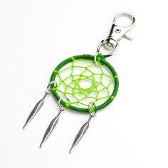 Bijou de sac / Porte clé attrape rêve artisanal vert  Ce bijou de sac est composé d'un cercle tissé avec fils de cotons et de 3 plumes en métal argenté, ce produit est confectionné en un seul exemplaire.  Taille de la plume : 29 mm Taille du cercle : 38 mm