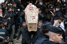 Jan. 15, 2015. Pallbearers carry the casket of Charlie Hebdo cartoonist Bernard Verlhac, known as Tignous, decorated by friends and colleagues of the satirical newspaper Charlie Hebdo, at the city hall of Montreuil, outside east of Paris. Photo: Michel Euler