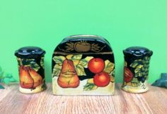 "Winter Fruit Salt and Pepper Shakers with Napkin Holder by ACK. $15.00. 3 Pc Set. Microwave and Dishwasher Safe. Hand painted ceramic. Ack Winter Fruit Design. Makes a Great Gift Idea. New 3PC Winter Fruit Salt and Pepper Shakers with a Napkin Holder. Background is black and accented with fruits which are apple, pear, grapes. Napkin holder measures approximately 5"" x 4.5"" with shakers being 2.5"" x 3.5"". Very Nice Collection."