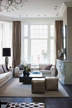 Een woonkamer in modern klassieke stijl. De kamer heeft ontzettend mooie hoge ramen. Door de kroonluchter, de luxe stoffen en de elegante schouw ontstaat echt die klassieke sfeer.