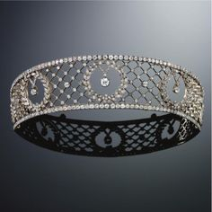 AN ANTIQUE DIAMOND BANDEAU TIARA circa 1890. Of diamond-set trelliswork design, the three central old-cut diamond collets suspended within diamond laurel wreath to the diamond line border, mounted in silver and gold.