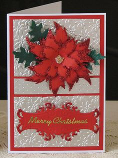 Silver paper embossed with poinsettia (or daisy?) folder, cut in half, Swiss dots embossed strip across middle, fancy label with red glitter, hand made poinsettia. Die cut leaves.