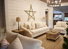 Living area with white couches and chicken coop coffee table from @simplysoutherncottage.