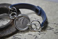 Hand painted blue leather coin bracelet.  The coin is a 1976 1 Franc from France.  The findings are silver plate and the closure is a snap. The leather used in this is from a recycled belt.