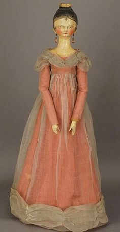 Early 19th century Grodnertal doll with a trunk and wardrobe, including bonnets.