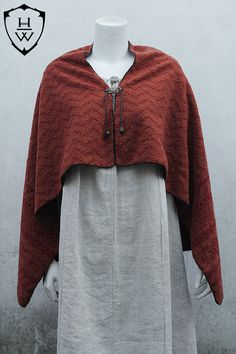 This cape is perfect for reenactment or larpers that look for a more accurate garment for their Viking or Saxon or medieval outfits. The wool capes were a protection against harsh weather conditions and commonly used by men and women. This cape is made of tufted non laminated wool in the shades of brick orange and deep red. The hems are hand stitched with cotton red thick string and trimmed with green wool. It fastens with a cotton green string trough eyelets trimmed with two brass beads…
