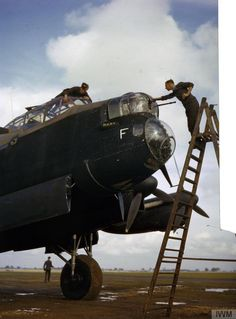An armourer cleans the .303in Brownings in the front turret of Avro Lancaster R5666/`KM-F' of No. 44 Squadron while another member of the ground crew cleans the cockpit windows, Waddington, October 1942