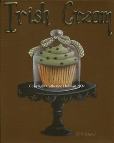 A white chocolate chip cupcake is piled high with piped green Irish Cream frosting and topped with miniature chocolate chips. Displayed on a