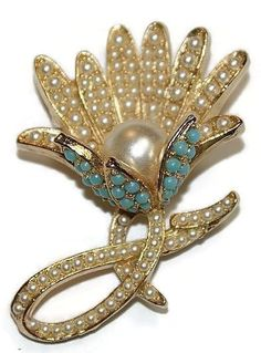 This is a lovely 3 dimensional pin signed ART with the copyright symbol. The pin is bright and shiny. Faux pearls.