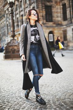 Andy Torres goes rocker-casual in high-rise ripped jeans, graphic tee, chunky boots, and a long luxurious coat.