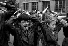 """Main sur la tête, Montreuil sous Bois, 1958. """"A Montreuil, il vivait dans la zone, un petit marginal, une terreur, inacceptable en classe dont il était exclu , il passait donc le plus clair de son temps dans la cour, étant prof de gym et travaillant donc dans la cour, nous cohabitions à longueur de journée. Il possédait un stock, d'insultes extraordinaire. Ferme ta gueule v'la le marchand d'os! Il créait la révolution partout où il passait! """" © Marc Held / VOZ'Galerie."""