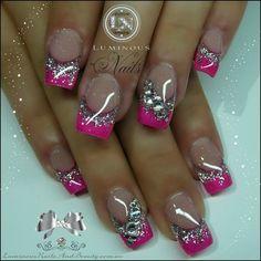 Estilosas uñas con las puntas decoradas en rosa fucsia, decoradas con brillos plateados y piedras cristalinas.